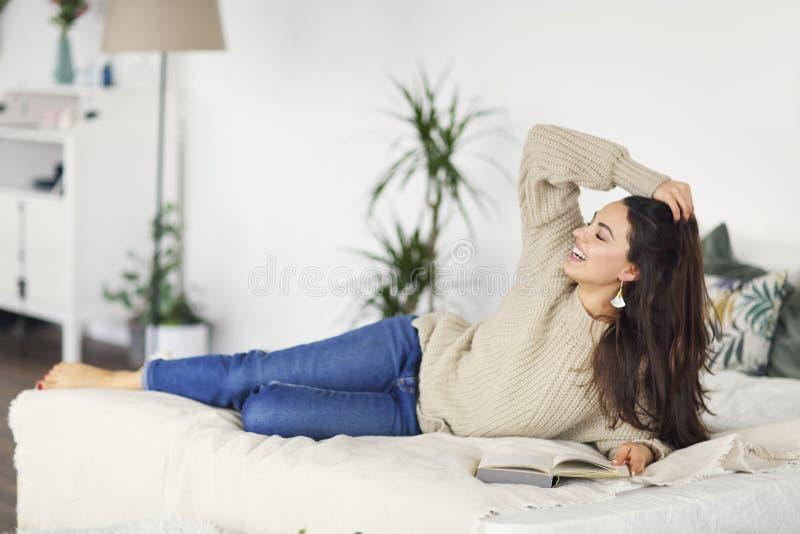 Junge glückliche brunette Frau mit tragender Strickjacke des Buches stockfoto