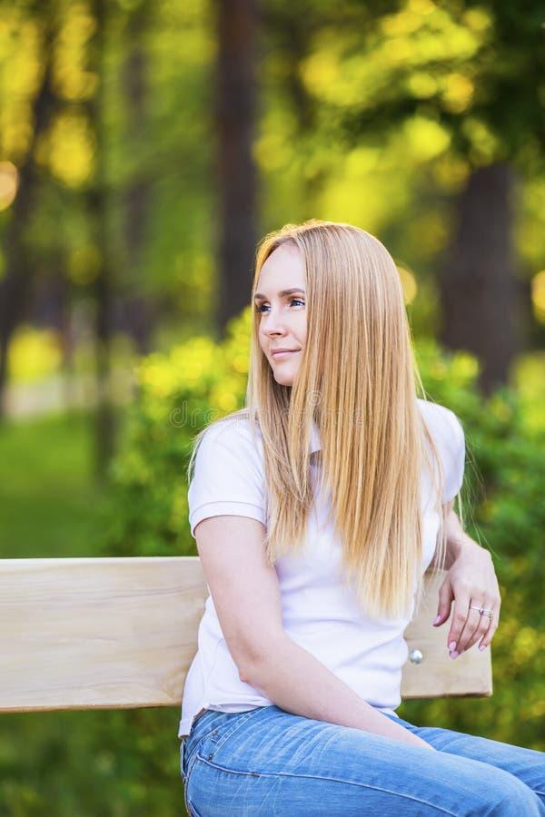 Junge, glückliche, dünne junge blonde Frau mit dem langen schönen Haar, lächelnd, im Sommerpark unter den Strahlen der Sonne lizenzfreie stockbilder