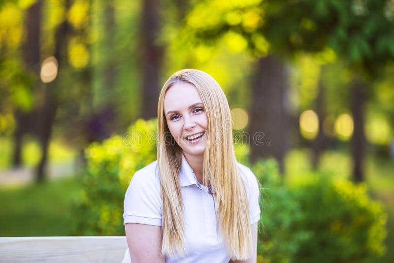 Junge, glückliche, dünne junge blonde Frau mit dem langen schönen Haar, lächelnd, im Sommerpark unter den Strahlen der Sonne stockfotografie