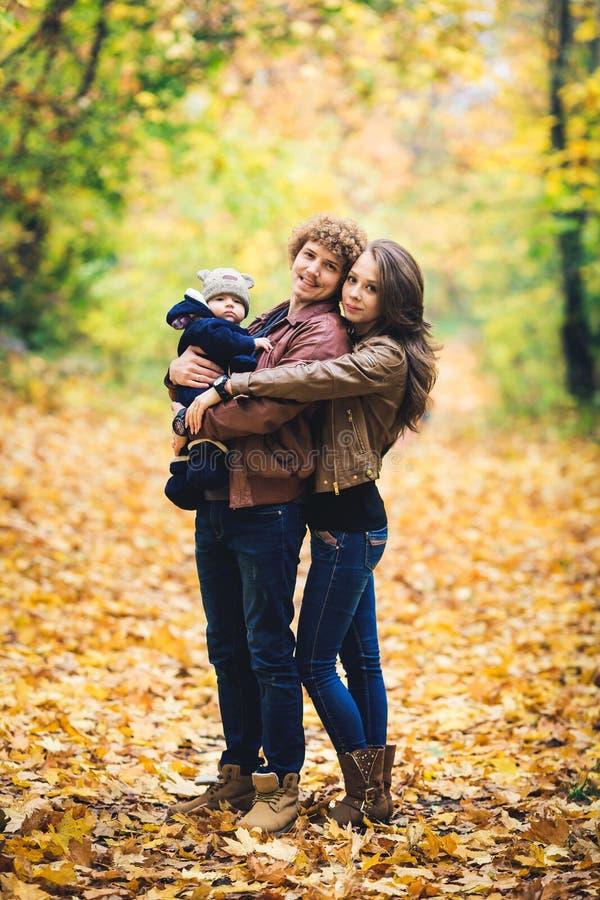 Junge glückliche Familie, die im Herbst im Park umarmt lizenzfreie stockfotografie