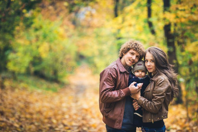 Junge glückliche Familie, die im Herbst im Park umarmt stockfotografie