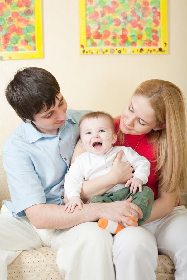 Junge glückliche Familie, die zu Hause auf Sofa sitzt stockfoto