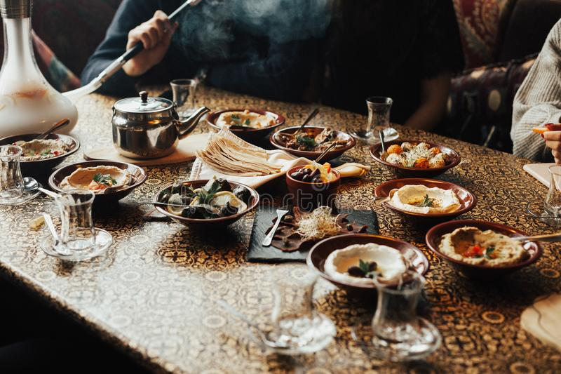 Junge glückliche Firma von Leuten isst der Libanon-Lebensmittel und smokinh shisha Der Libanon-Küche lizenzfreies stockfoto