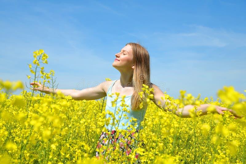 Junge glückliche Frau auf blühendem Rapssamenfeld stockfotografie