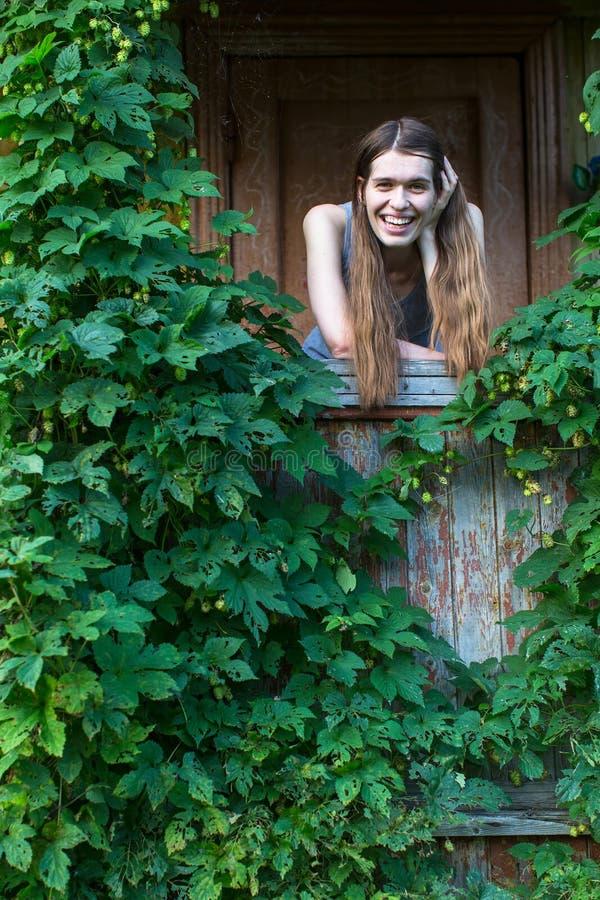 Junge glückliche Frau auf dem Portal eines Landhauses unter dem Grün stockfotos