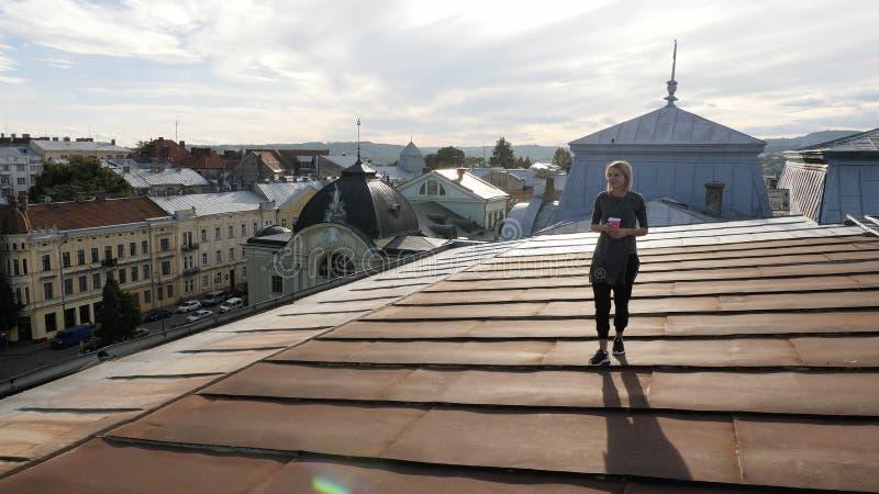 Junge glückliche Frau, die auf die Dachspitze mit Kaffee geht Wind, der ihr Haar durchbrennt lizenzfreie stockfotografie