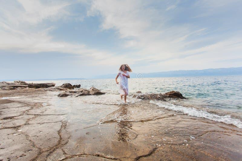 Junge glückliche Frau, die auf dem Strand läuft stockbild