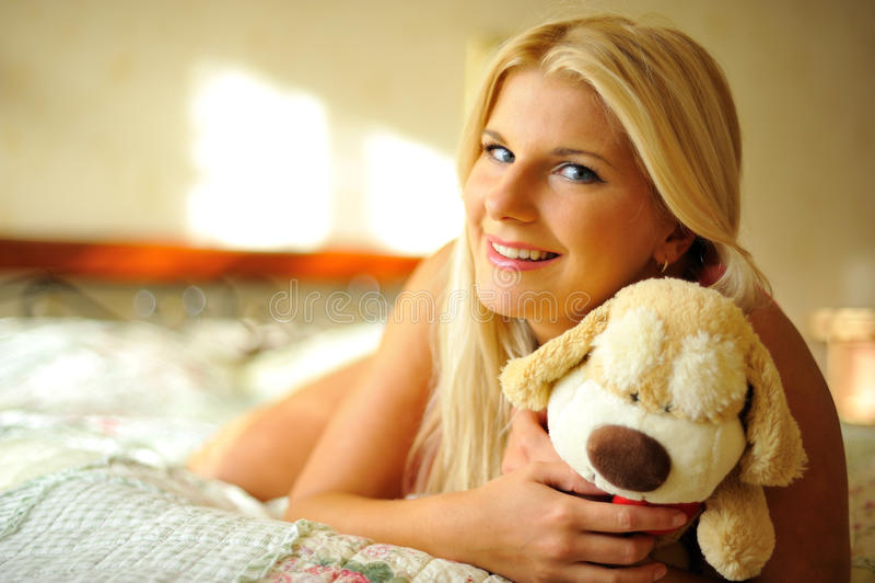 Junge glückliche Frau, die auf einem Bett sich entspannt stockfotografie