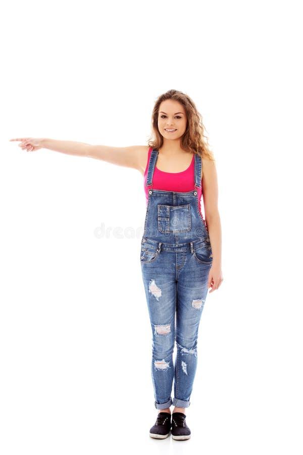 Junge glückliche Frau, die auf etwas zeigt stockfoto