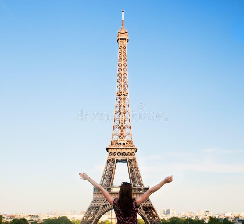 Junge glückliche Frau, die den Eiffelturm, Paris, Frankreich gegenüberstellt stockfotografie