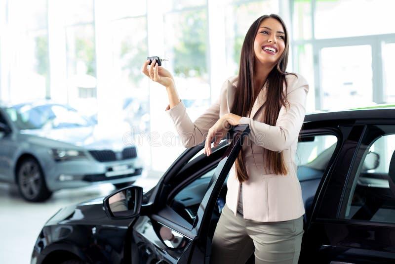 Junge glückliche Frau, die den Schlüssel des Neuwagens zeigt stockfotografie