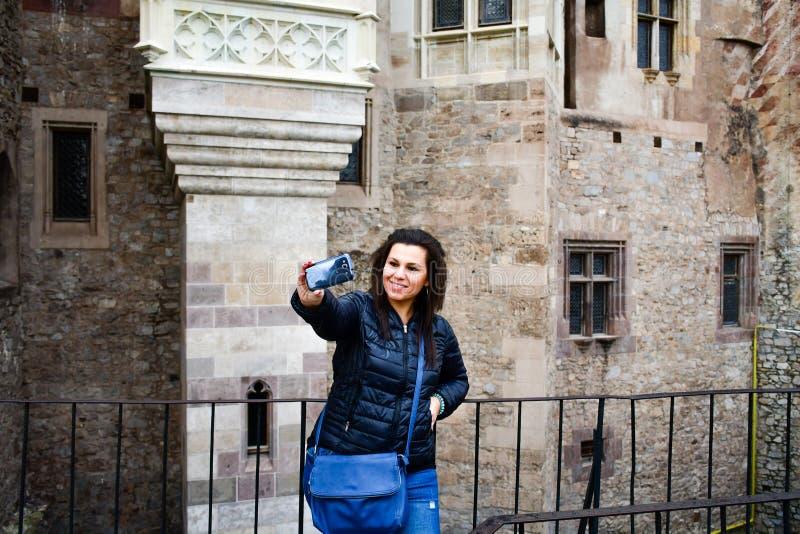 Junge glückliche Frau, die ein selfie an Corvin-Schloss, Rumänien nimmt lizenzfreies stockbild