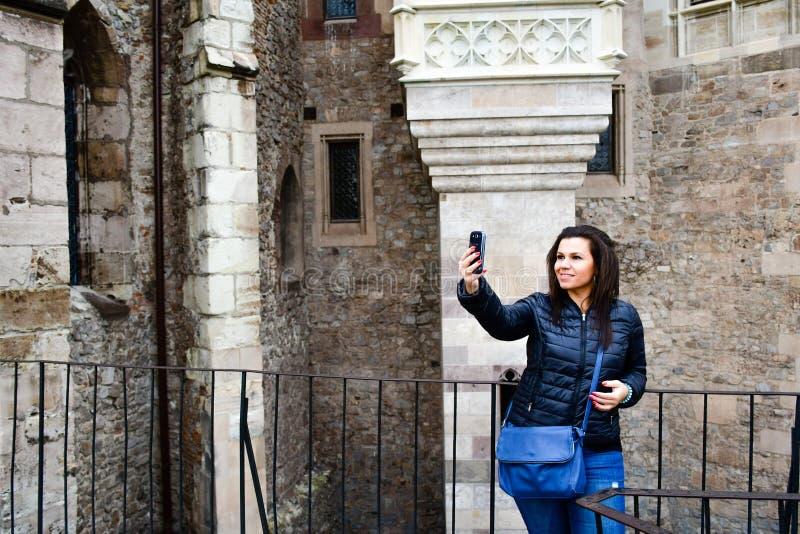Junge glückliche Frau, die ein selfie an Corvin-Schloss, Rumänien nimmt lizenzfreies stockfoto