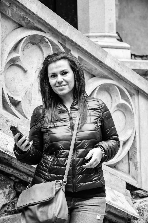 Junge glückliche Frau, die einen Smartphone an Corvin-Schloss, Rumänien verwendet stockfotos