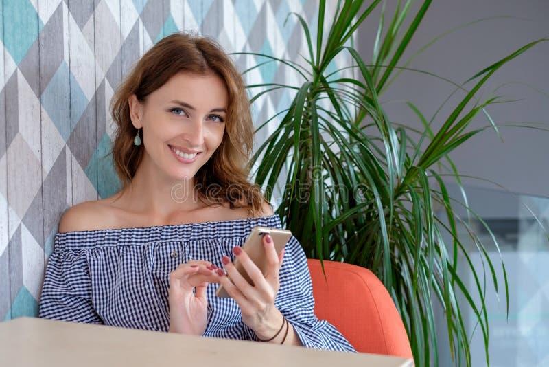Junge glückliche Frau, die am Handy mit Freund beim im modernen Kaffeestubeinnenraum allein sitzen, lächelnd spricht stockbilder