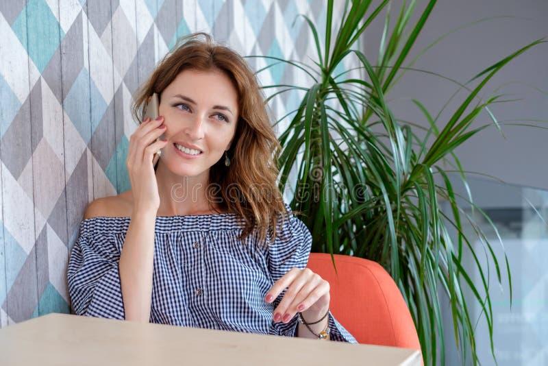 Junge glückliche Frau, die am Handy mit Freund beim im modernen Kaffeestubeinnenraum allein sitzen, lächelnd spricht lizenzfreies stockbild