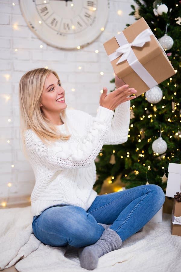 Junge glückliche Frau, die im Wohnzimmer mit verziertem Christma sitzt stockbilder