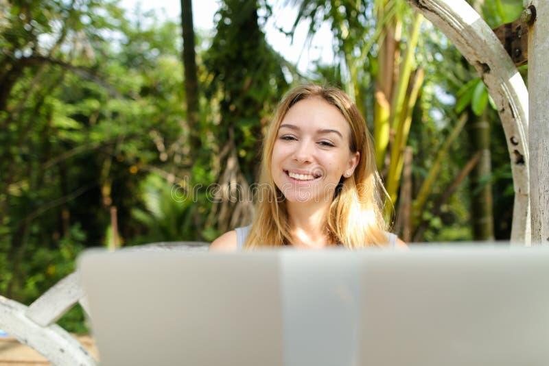 Junge glückliche Frau, die Laptop, Palmen im Hintergrund verwendet lizenzfreie stockfotografie