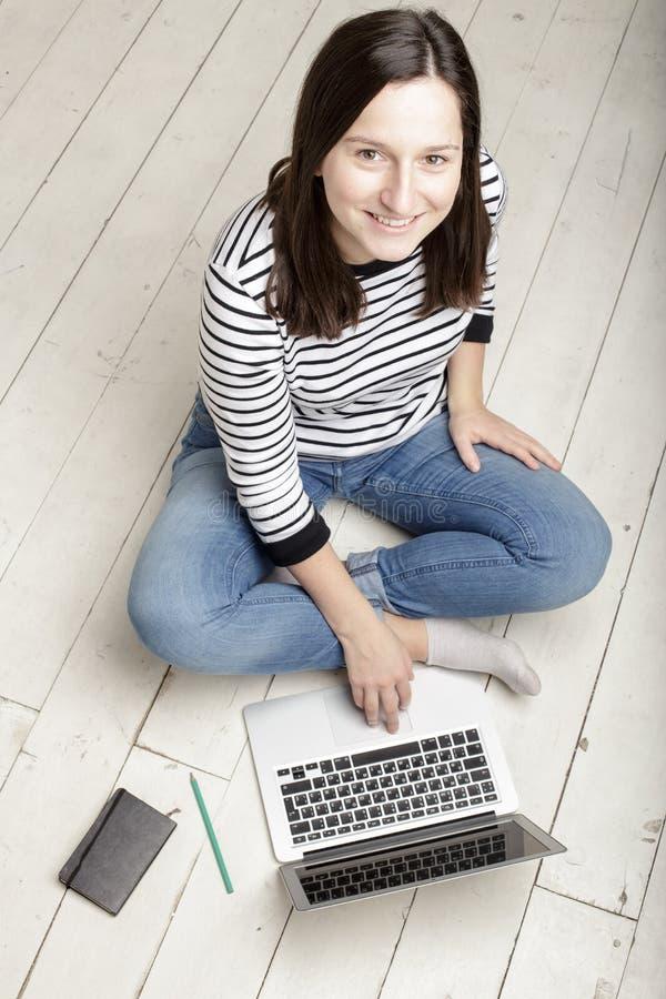 Junge glückliche Frau, die mit einem Laptop sitzt auf einem weißen woode arbeitet stockbild