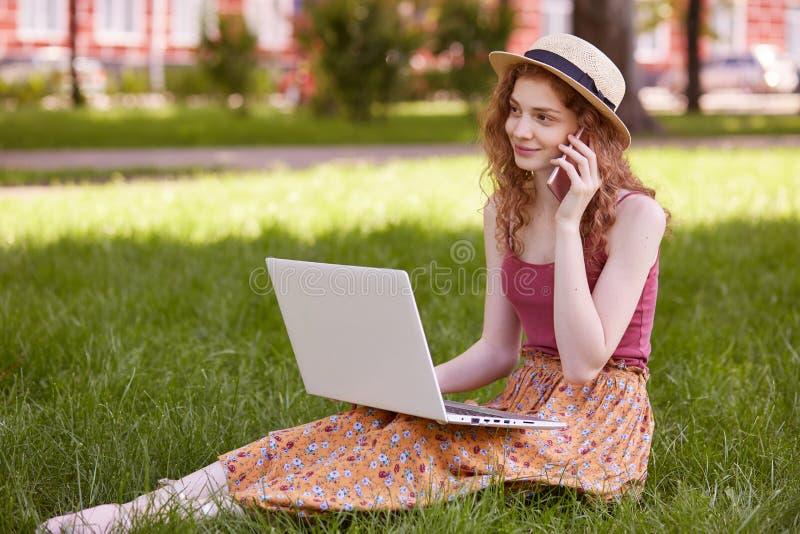 Junge glückliche Frau, die mit intelligentem Telefon beim Machen der Pause zwischen Arbeit über Laptop-Computer, lächelnde Studen stockfoto