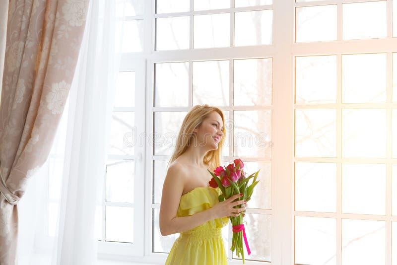 Junge glückliche Frau, die mit Tulpenbündel im gelben Kleid, Sonnenlicht lächelt lizenzfreie stockbilder