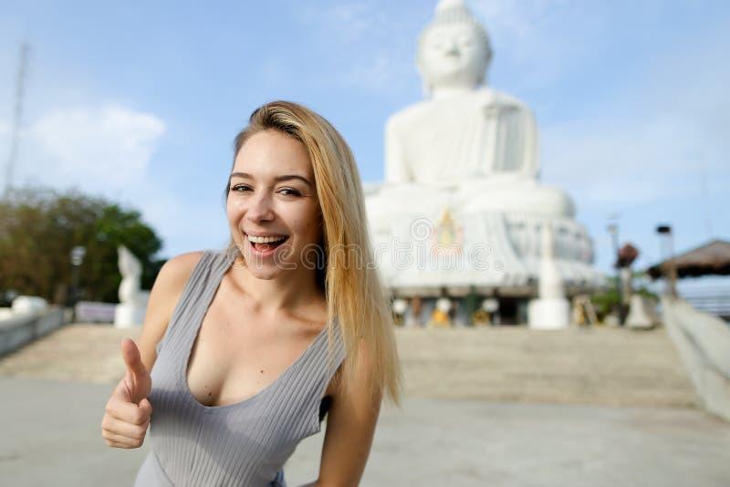 Junge glückliche Frau, die oben Daumen, weiße Buddha-Statue in Phuket im Hintergrund zeigt lizenzfreie stockbilder