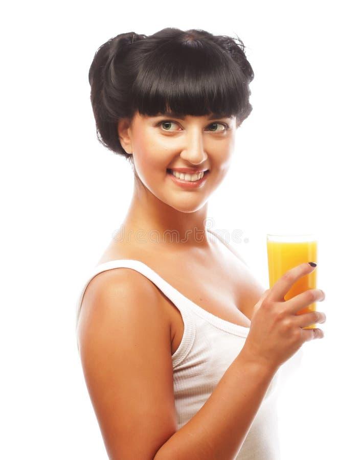 Junge glückliche Frau, die Orangensaft trinkt stockbilder
