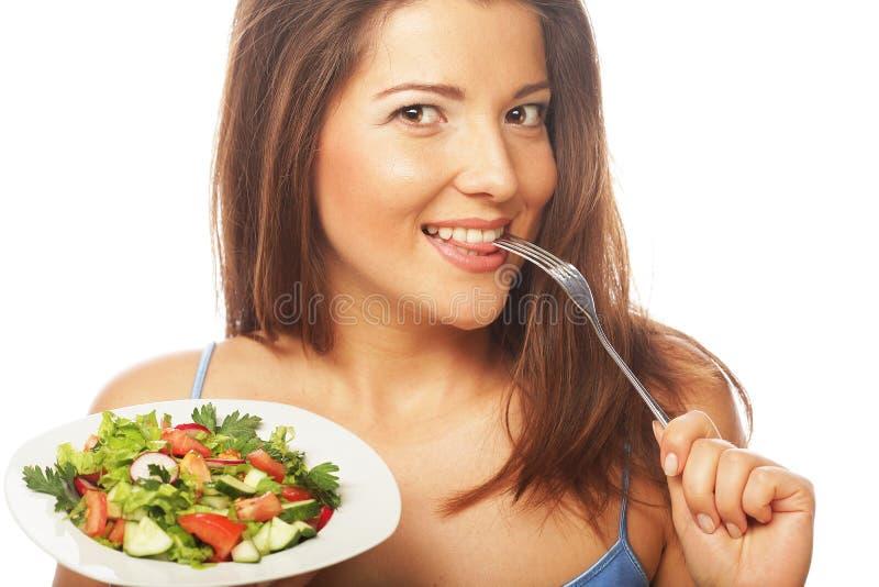 Junge glückliche Frau, die Salat isst. lizenzfreies stockbild