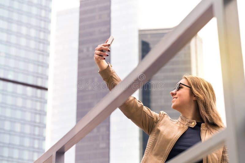 Junge glückliche Frau, die selfie in der Stadtstraße nimmt lizenzfreie stockfotografie