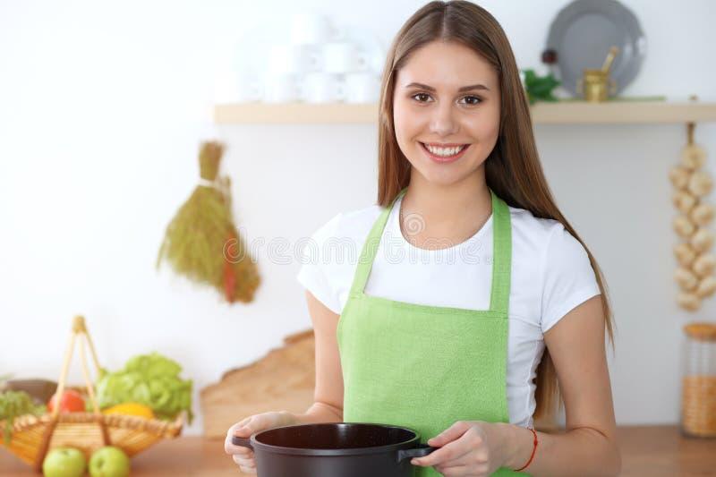 Junge glückliche Frau, die Suppe in der Küche kocht Gesunde Mahlzeit, Lebensstil und kulinarisches Konzept Lächelndes Kursteilneh stockbild
