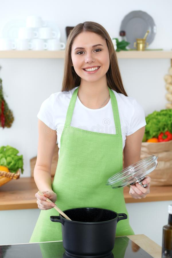 Junge glückliche Frau, die Suppe in der Küche kocht Gesunde Mahlzeit, Lebensstil und kulinarisches Konzept Lächelndes Kursteilneh lizenzfreie stockfotos