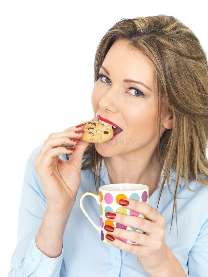 Junge glückliche Frau, die Tee und Kekse genießt stockbild