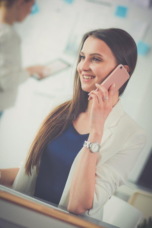Junge glückliche Frau, die am Tisch mit Laptop sitzt und am Telefon spricht lizenzfreies stockfoto