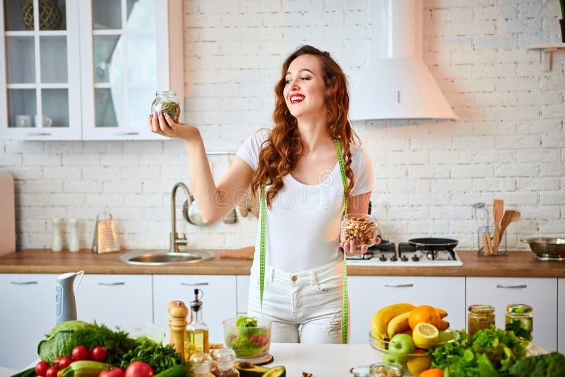 Junge glückliche Frau, die verschiedene Nüsse Acajoubaum, Haselnuss, Mandel in der modernen Küche isst Gesundes Lebensmittel und  stockbild