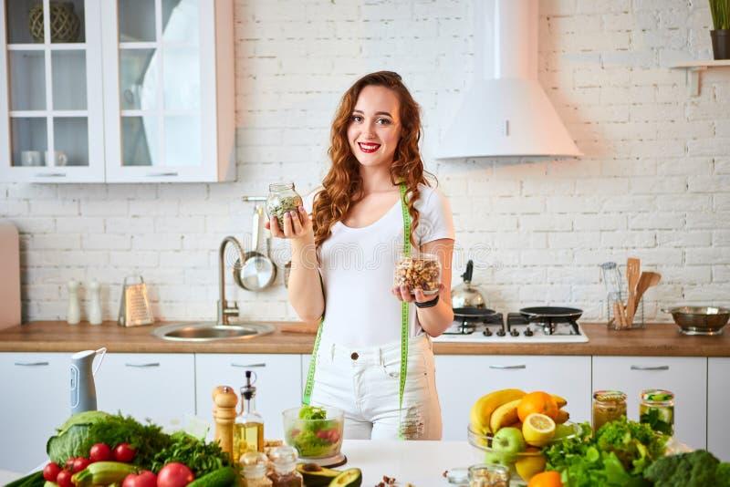 Junge glückliche Frau, die verschiedene Nüsse Acajoubaum, Haselnuss, Mandel in der modernen Küche isst Gesundes Lebensmittel und  lizenzfreie stockfotos