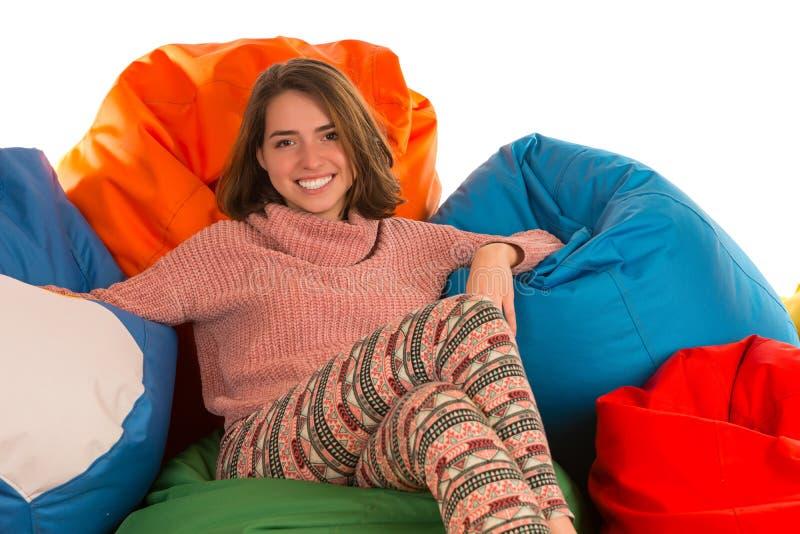 Junge glückliche Frau, die zwischen Sitzsackstühlen sitzt stockbilder