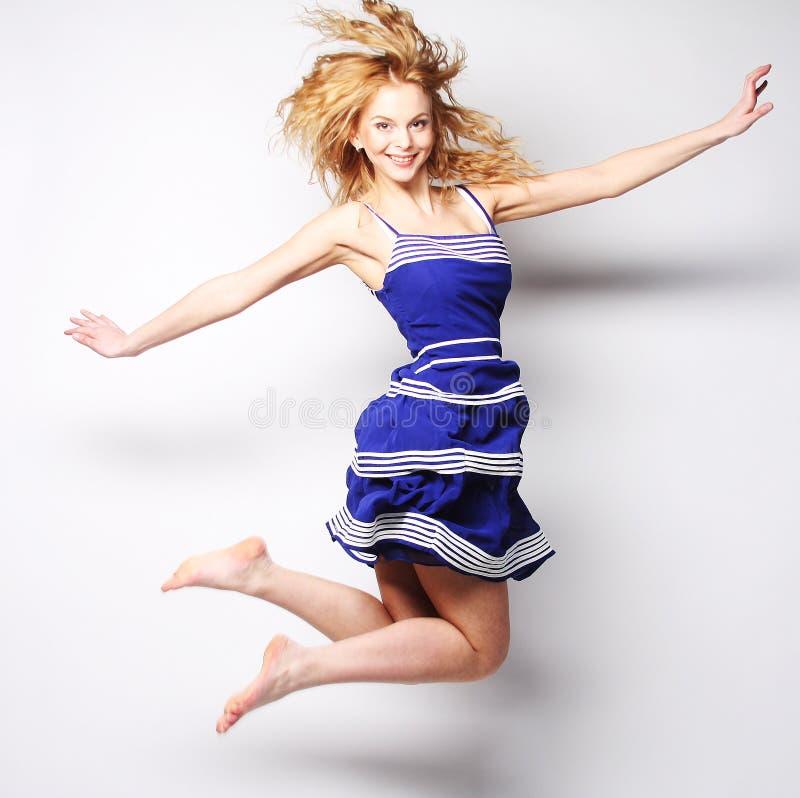 Junge glückliche Frau im blauem Kleiderspringen lizenzfreies stockfoto