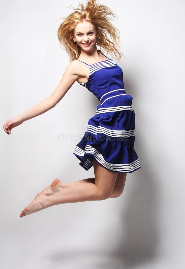 Junge glückliche Frau im blauem Kleiderspringen stockfoto