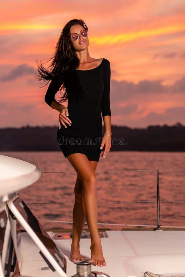 Junge glückliche Frau im schwarzen Kleid, das bei Sonnenuntergang auf der Yacht aufwirft stockbild