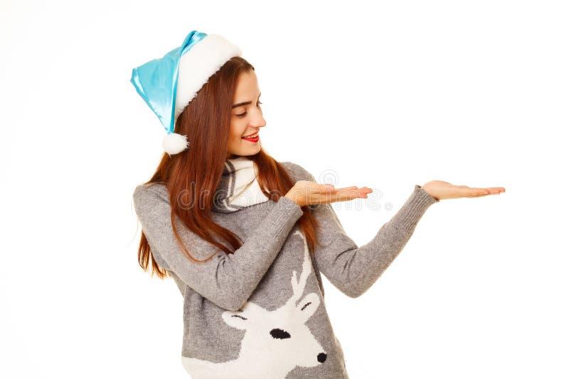 Junge glückliche Frau im warmen sweather, das Ihr Produkt über wh hält stockfoto