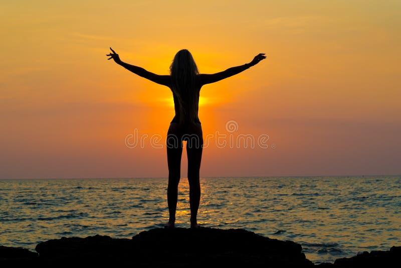 Junge glückliche Frau mit den angehobenen Händen stockfoto