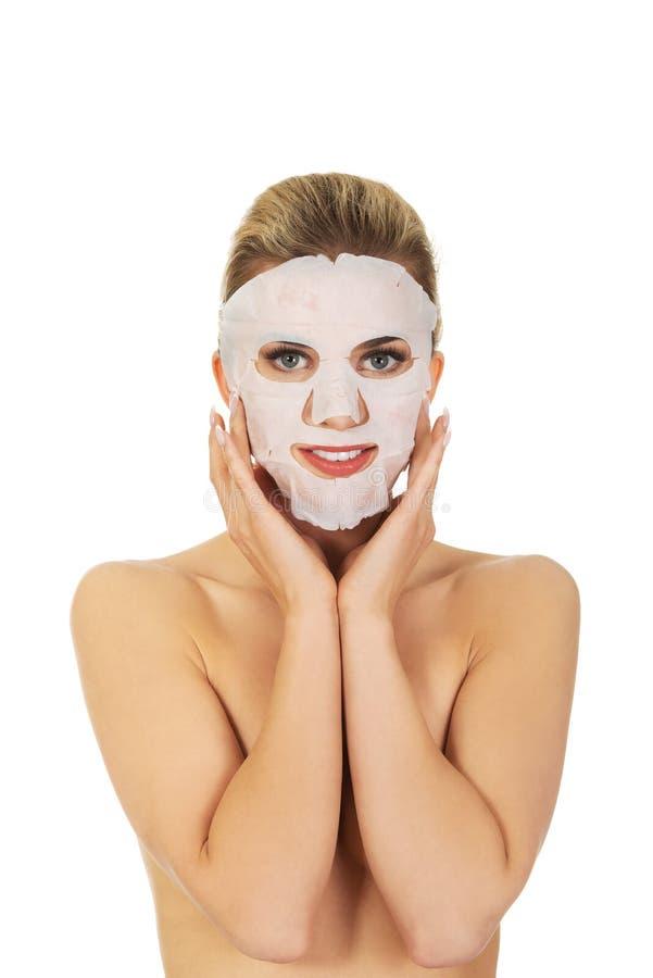 Junge glückliche Frau mit Gesichtsmaske lizenzfreie stockfotos
