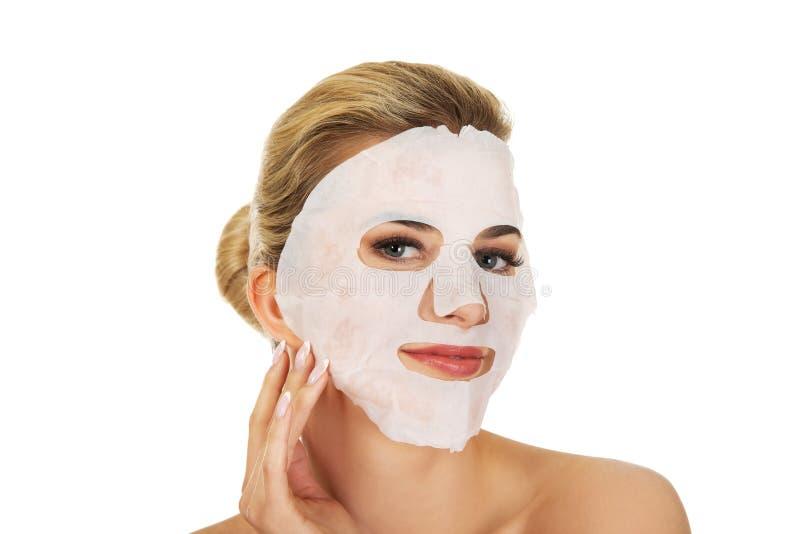 Junge glückliche Frau mit Gesichtsmaske stockfotografie