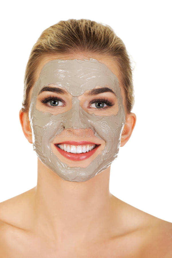 Junge glückliche Frau mit Gesichtsmaske lizenzfreie stockfotografie