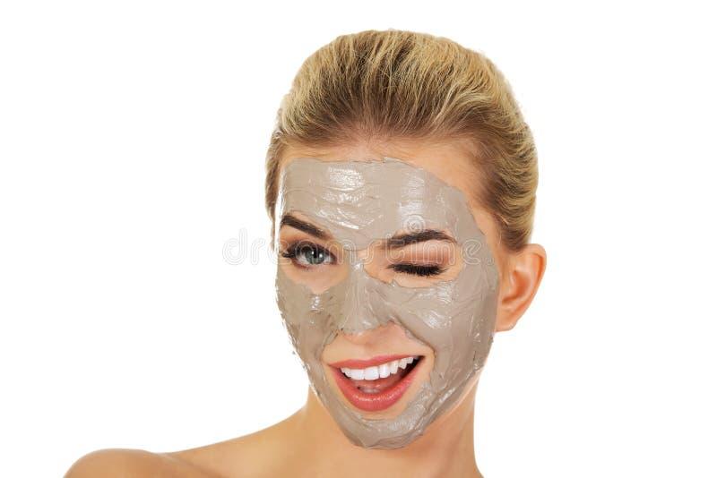 Junge glückliche Frau mit Gesichtsmaske lizenzfreies stockfoto