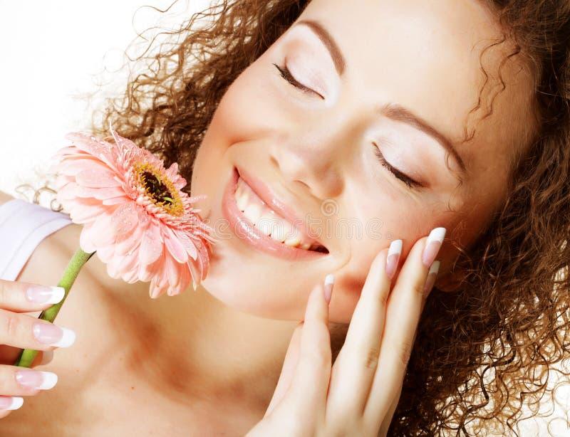 Junge glückliche Frau mit rosa Blume lizenzfreie stockbilder