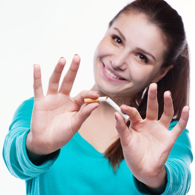 Junge glückliche Frau mit unterbrochener Zigarette stockbild