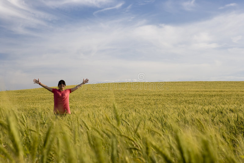 Junge glückliche Frau mitten in dem Feld lizenzfreies stockfoto