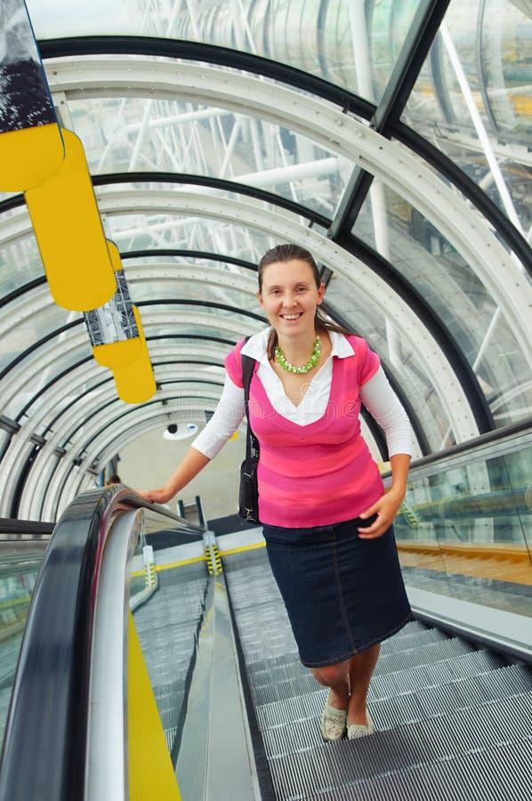 Junge glückliche Frau steigt auf die Rolltreppe stockbilder