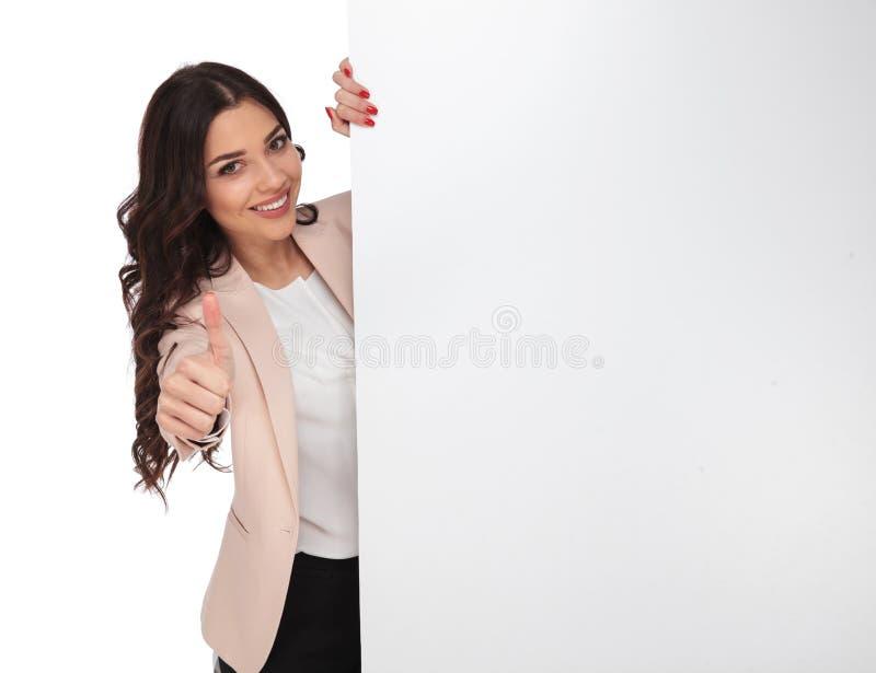 Junge glückliche Frau, welche die Anzeige empfiehlt, die sie zeigt stockbild